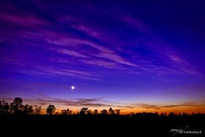 An orange, purple and blue sky above nature reserve De Teut in Zonhoven, Belgium during dusk