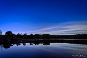 A night view of a pond in nature reserve De Teut in Zonhoven, Belgium with some whisks of clouds in the sky