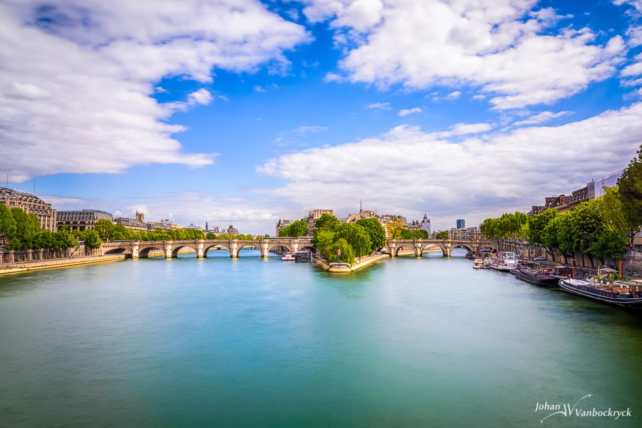 A view of Île de la Cité, Paris, France under a partly cloudy sky as seen from the Pont des Arts