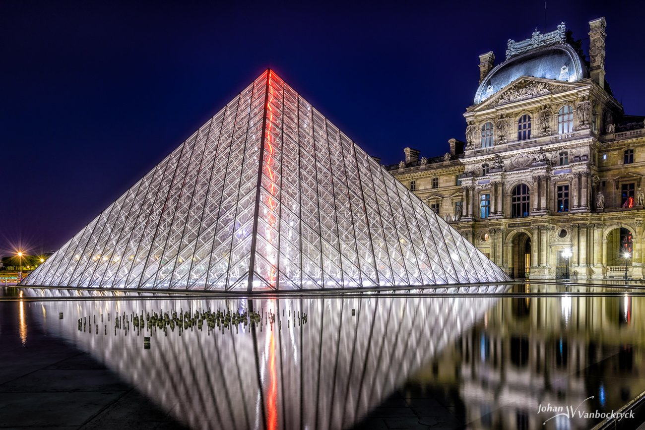 The glass pyramid of the Louvre with its reflection inthe water in Paris, France by night