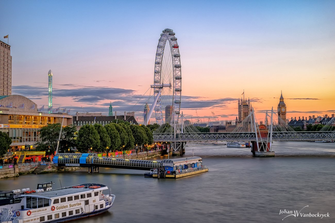 A view of the London Eye with Big Ben and the Palace of Westminster in the background during sunset