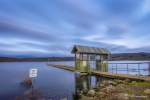 A morning view of a pier at the Laacher See in Germany with a sign to not feed the birds