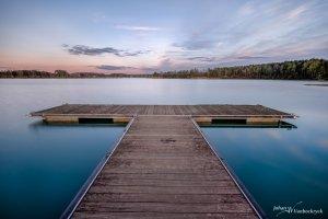 A pier in the water of De Plas in Kelchterhoef, Houthalen-Helchteren, Belgium during sunset