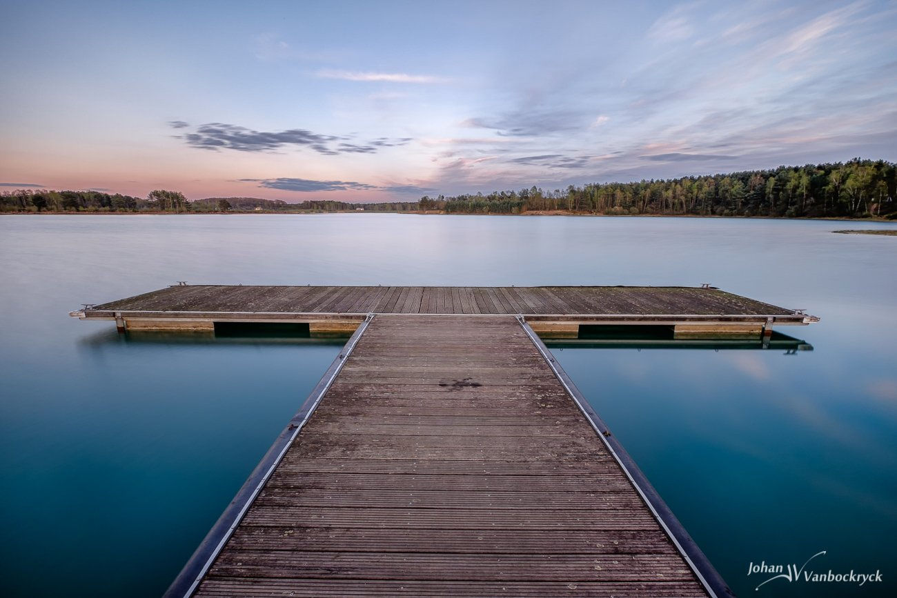 A pier in the water of De Plas in Kelchterhoef, Houthalen-Helchteren, Belgium during sunset