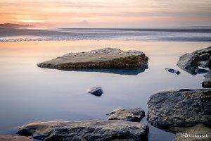The rocks of a groyne in the seawater during sunset in Koksijde, Belgium