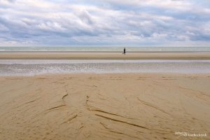 Two joggers in the distance on the beach of Koksijde, Belgium
