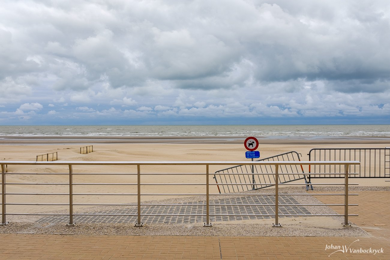 Railings at the edge of the promenade of Koksijde, Belgium with a cloudy sky above the beach