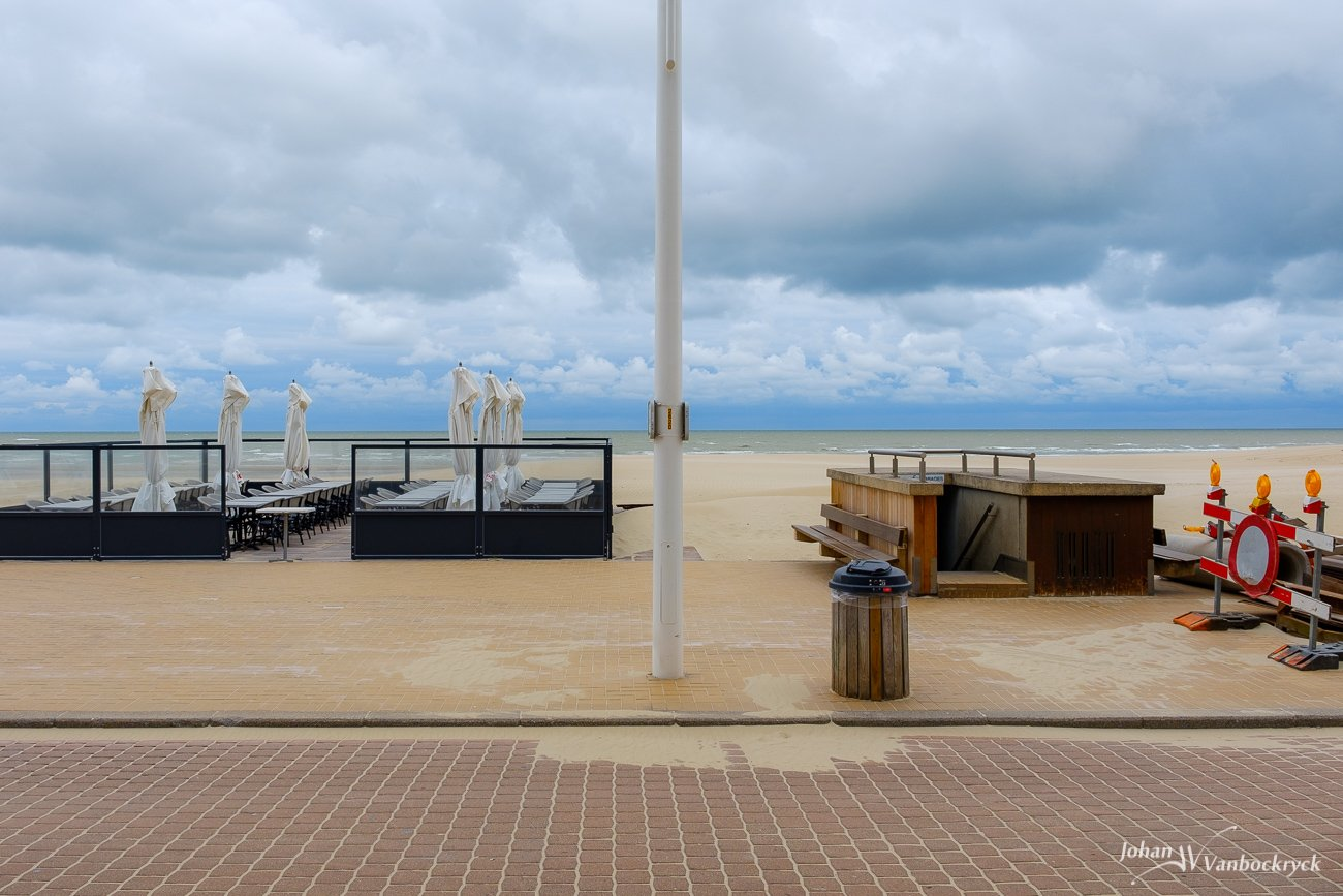 A view from the promenade towards the beach in Koksijde, Belgium on a cloudy morning with an empty sidewalk cafe, a rubbish bin, a light pole and some construction signs