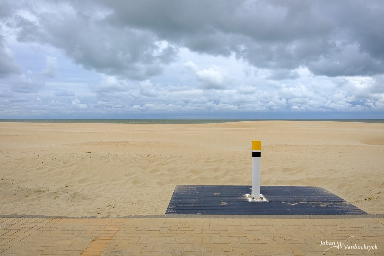 A pole at the edge of the promenade under a cloudy sky above the beach of Koksijde, Belgium