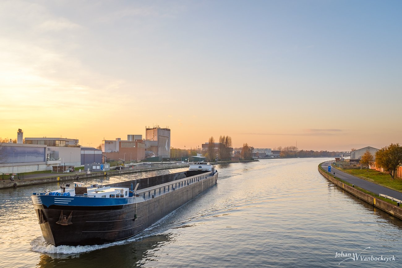 An empty barge during sunset on the Albertkanaal in Hasselt, Belgium, as seen from the bridge of the Kempische Steenweg