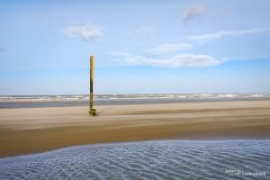 A tide pole on the beach of Koksijde, Belgium with a strong wind blowing the sand around