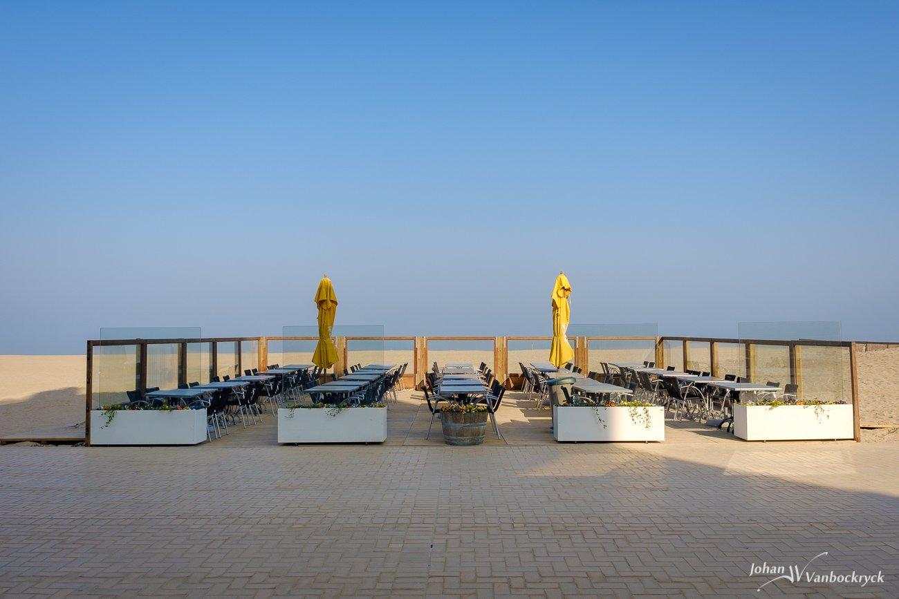 An empty sidewalk cafe with closed yellow umbrellas on the beach of Koksijde, Belgium