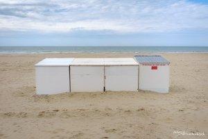 A row of beach cabins on the beach in Koksijde, Belgium under a cloudy sky