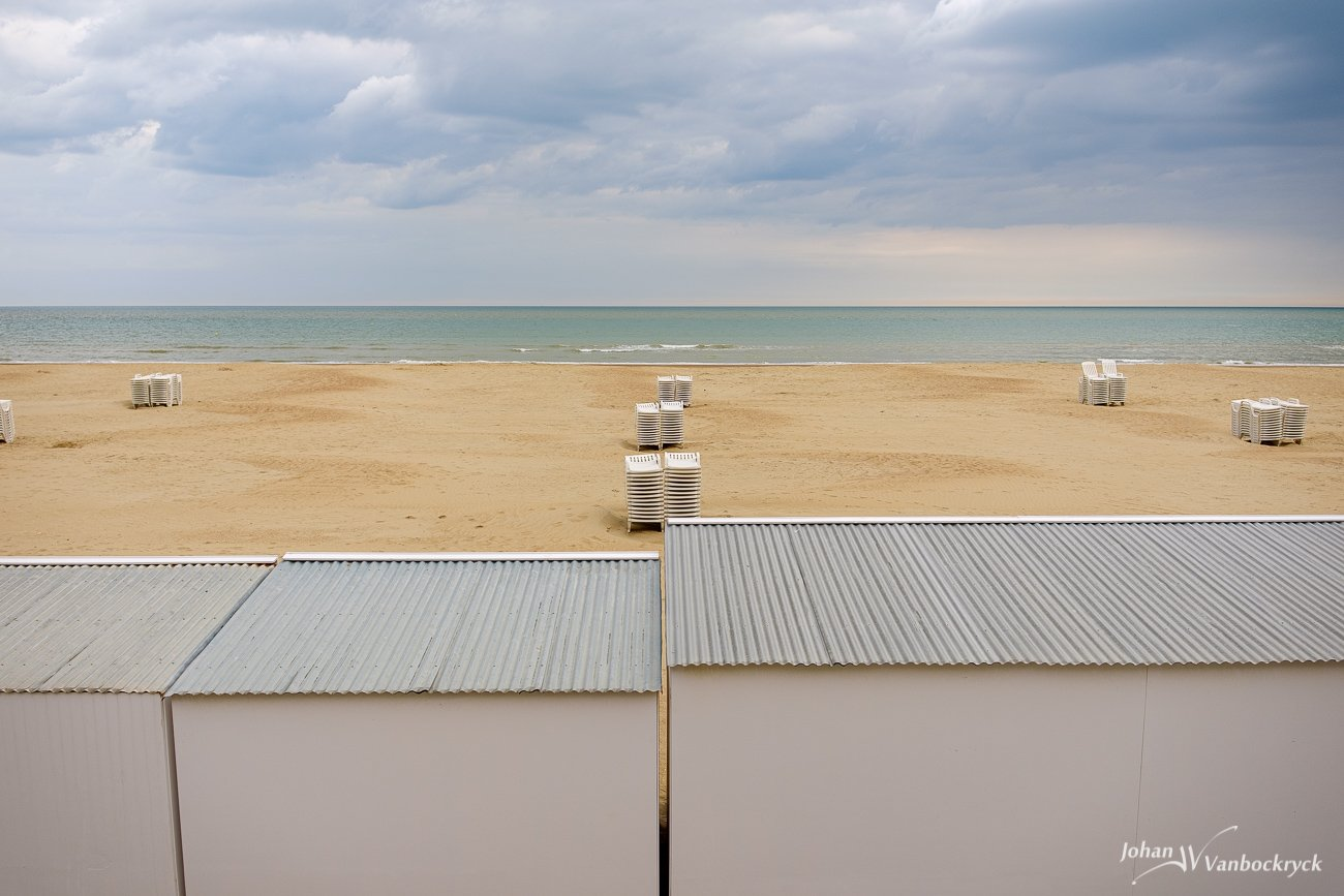 Stacked beach chairs on the beach of Koksijde, Belgium under a cloudy sky with beach cabins in the foreground