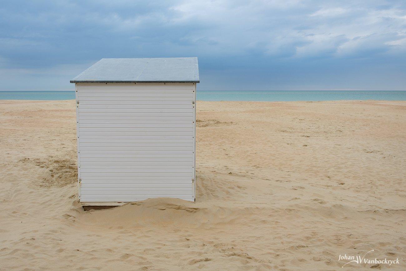 A beach cabin on the beach of Koksijde, Belgium under a cloudy sky