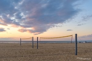 A volleyball field on the beach of Koksijde, Belgum during sunrise with some clouds in the sky