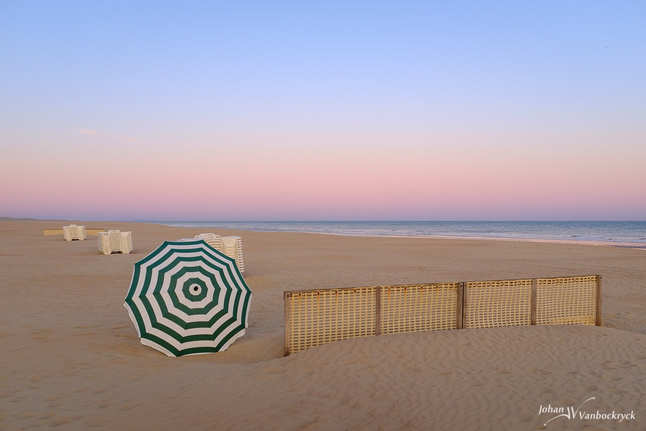 A parasol, fence and stacked beach chairs on the beach of Koksijde, Belgium during sunrise/dawn