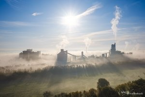 The industrial buildings of CBR in Visé, Belgium, covered by a low morning fog under a bright sun