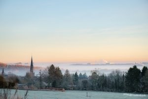 A view over frozen mist-covered area around Vaals, the Netherlands in the direction of Aachen during the sunrise