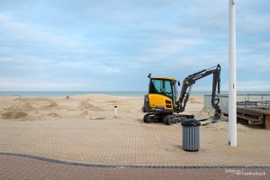 An excavator on the promenade of Koksijde, Belgium with a rubbish bin and light pole in the foreground, and the beach in the background