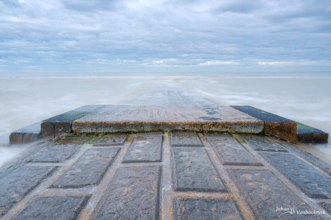 A groyne with the rising tide under a cloudy sky on the beach of Koksijde, Belgium