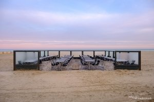 An empty sidewalk cafe during sunrise on the beach of Koksijde, Belgium