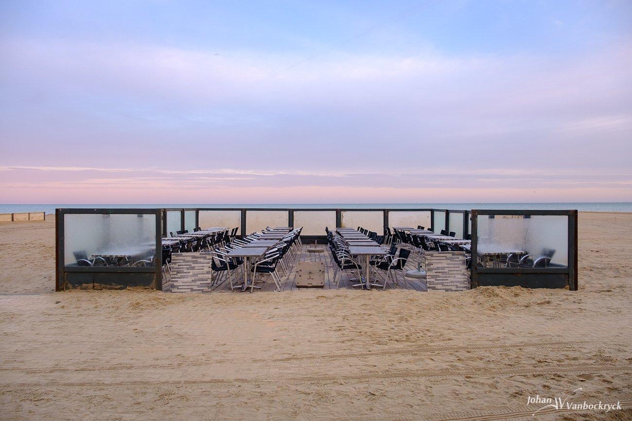 An empty sidewalk cafe during sunrise on the beach of Koksijde, Belgium