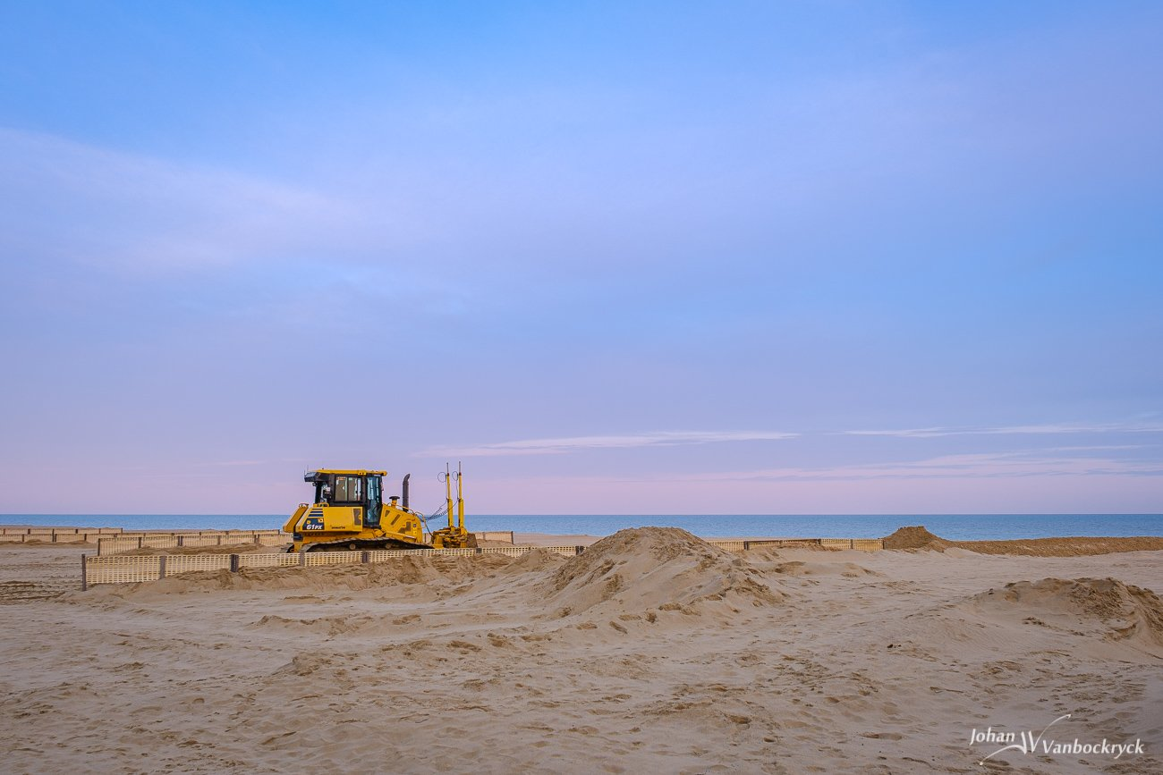 A bulldozer on the beach of Koksijde, Belgium during sunrise
