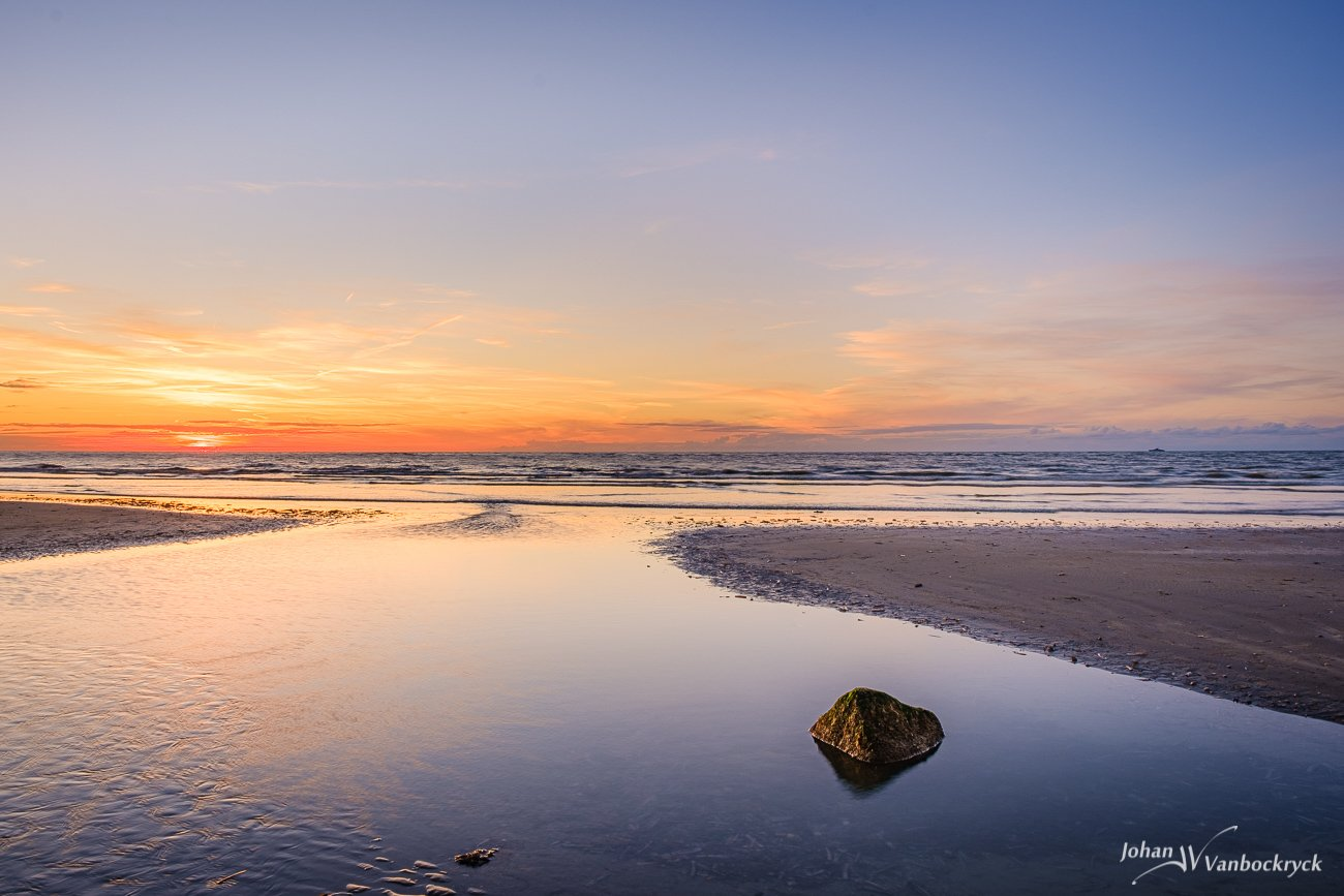 A sunset on the beach of Koksijde, Belgium with a stone in the water on the foreground