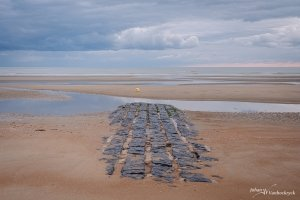 A groyne on the beach of Koksijde, Belgium under a cloudy sky