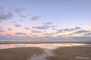 The beach of Koksijde, Belgium under a sunrise-coloured sky with some clouds