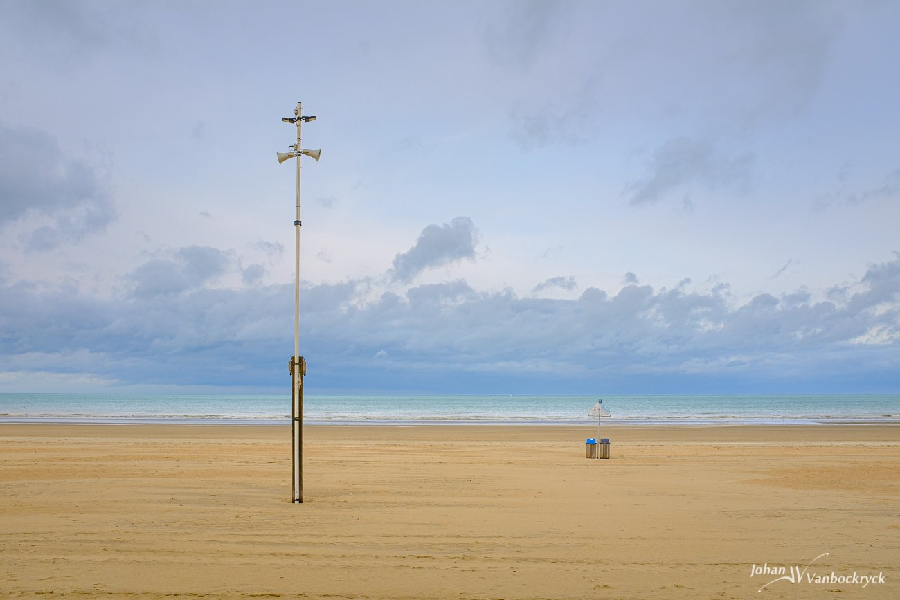 A pole megaphone and rubbish bins on the beach of De Panne, Belgium