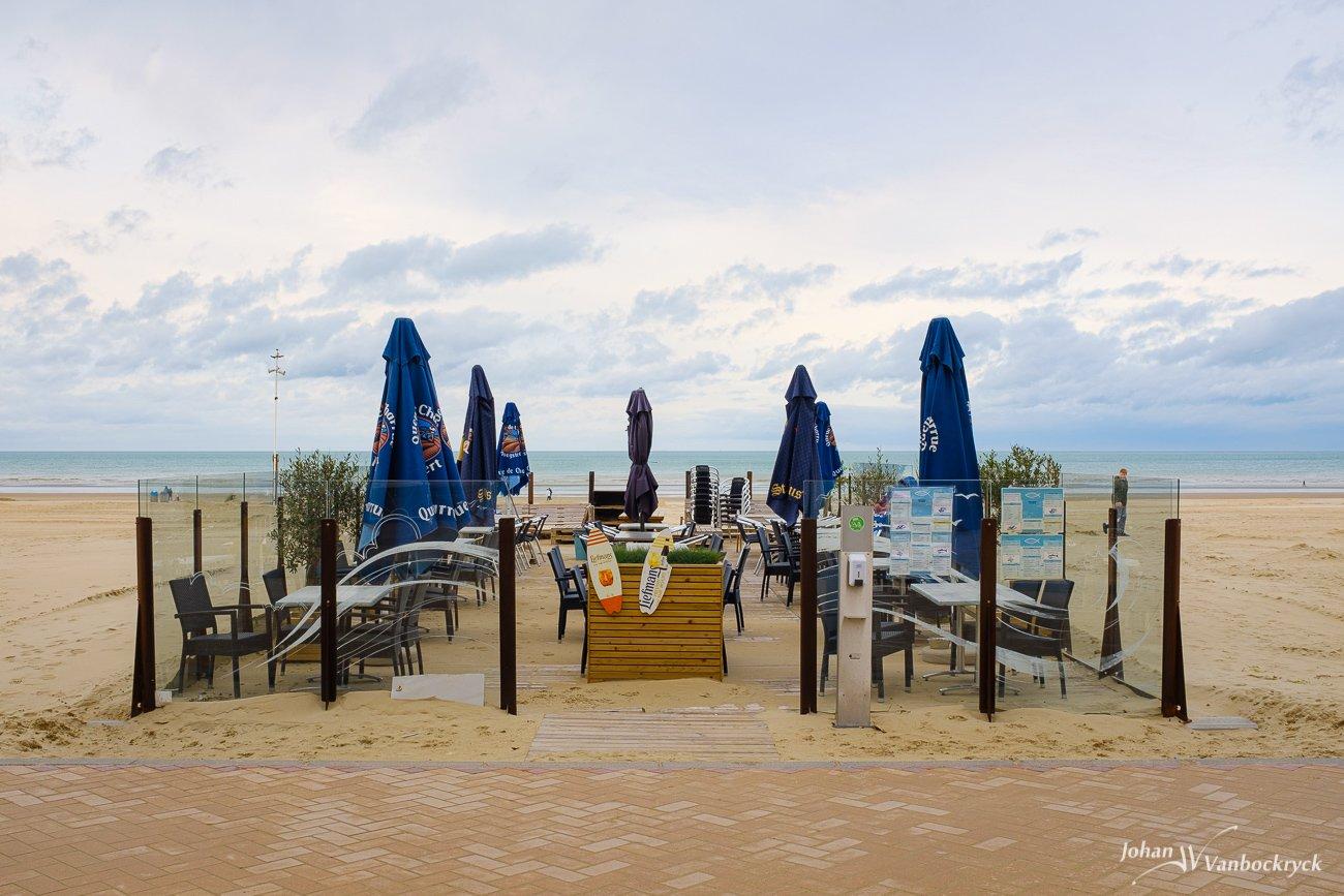 An empty sidewalk cafe with closed blue umbrellas on the beach of De Panne, Belgium