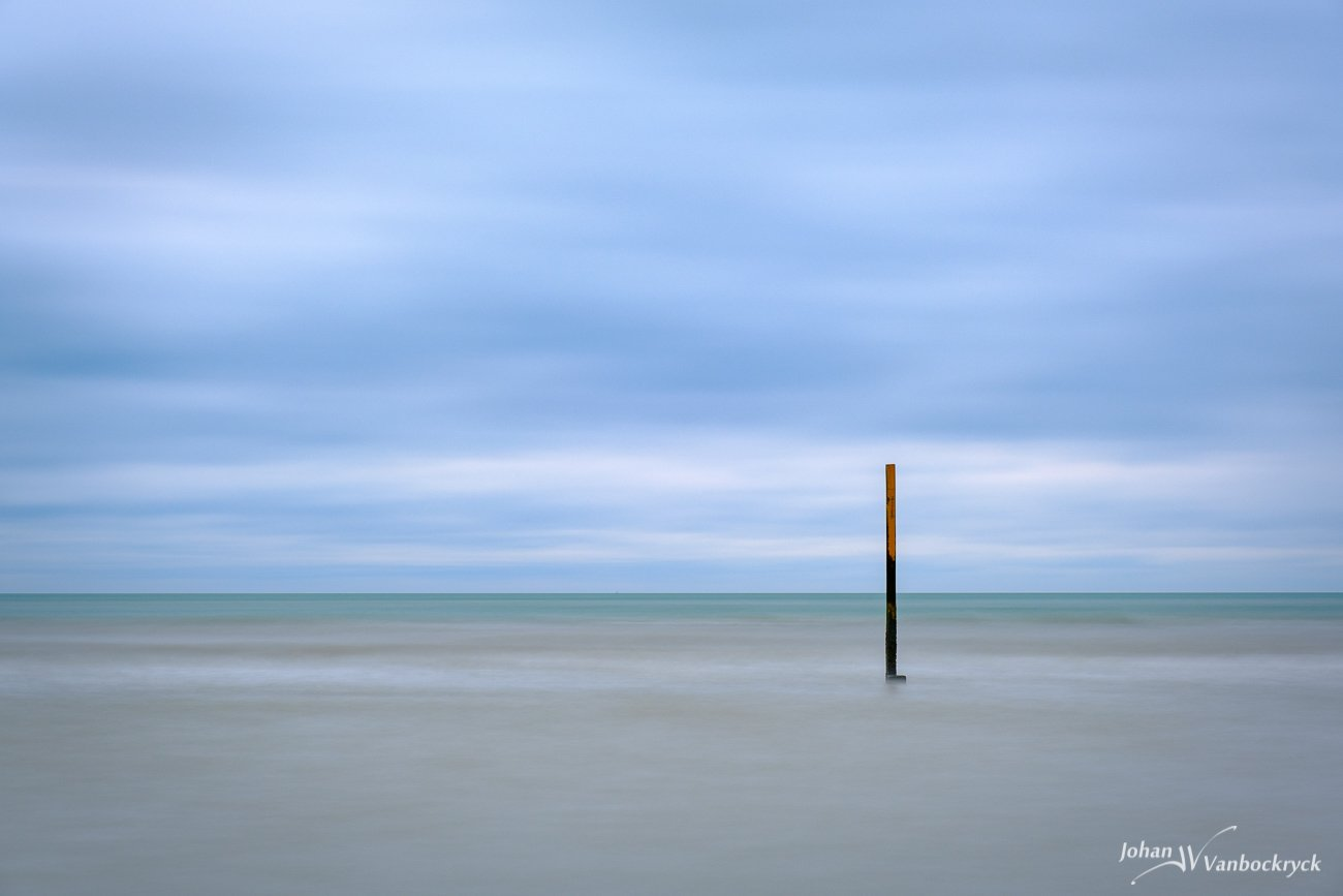 A tide pole in the North Sea at the beach of Koksijde, Belgium under a cloudy sky