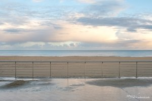 The railing of the wet promenade at the beach in Koksijde, Belgium in the morning